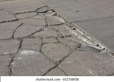 Broken concrete sidewalk needs repair.