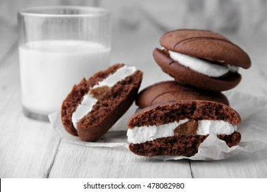 Broken cookies and stack of sponge cookies with cream on paper.glass with milk defosused on background