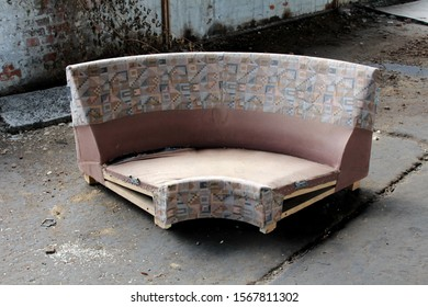 Broken cracked destroyed family house couch left at abandoned building ready for garbage surrounded with dirt and red brick wall on warm sunny summer day