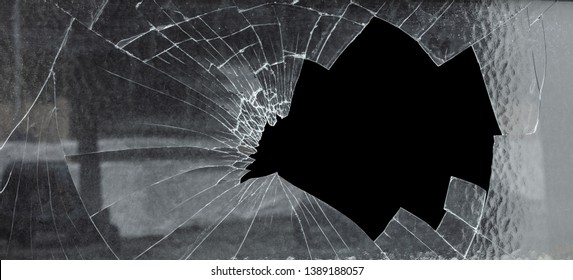 Broken Cracked Glass With Big Hole Against Black Background