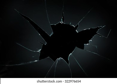 broken cracked glass with big hole over black background - Shutterstock ID 322976654