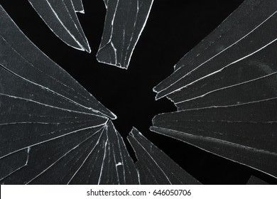 broken cracked glass with big hole over black background