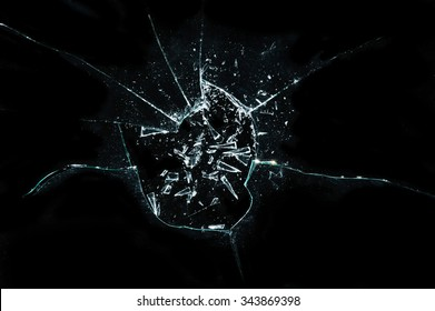 broken cracked glass with hole over black background