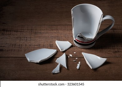 broken cup on wooden background
