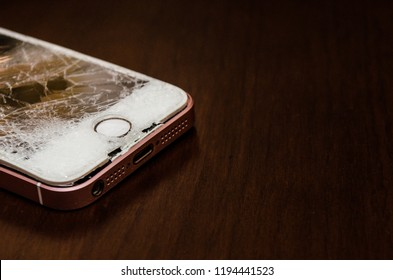 A broken and damaged Iphone SE, rose back and white screen, Cairo - Egypt. October 2018
