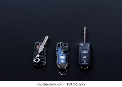 Broken or damaged remote key fob and new vehicle key on black dark grey background. Broken or damaged remote key fob of any vehicle car service.