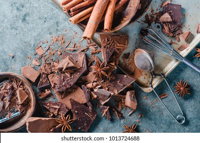 Broken dark chocolate, cinnamon and anise stars on a concrete background with a cocoa strainer and a whisk with glazing. Confectionery food photography.