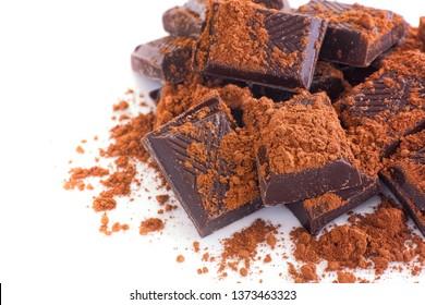 Broken dark chocolate with cocoa powder. White background.