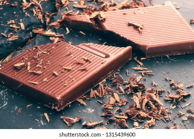 Broken dark chocolate and chocolate flakes on a wooden table