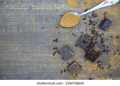 Broken dark chocolate pieces and cocoa powder on wooden background