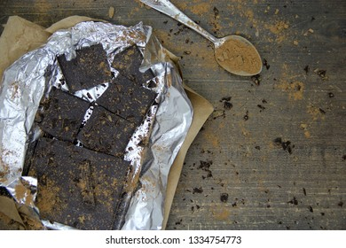 Broken dark chocolate pieces in wrapper and cocoa powder on wooden background