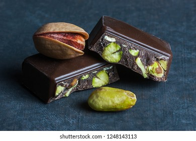 Broken and dark Pistachio Chocolate on black wooden rustic backdrop, composition of pistachios great for healthy and dietary nutrition. Concept of nuts and chocolates