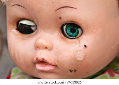 Broken doll crying. Concept Abandoned Person. Close up of an old doll`s face with tear