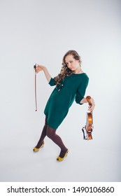 a broken doll in a green dress with a violin and a bow in her hands on a white background. tired girl-musician. The concept of advertising musical instruments, fashion, symbols