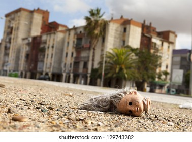 Broken doll head lying on the ground in a suburb on the outskirts of a mediterranean city