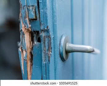 Broken door in blue and white colors after a burglery