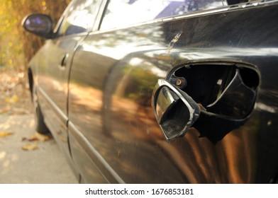 Broken door handle of a black car in the garage.