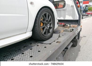 Voiture de voiture défoncée remorquée sur un camion de remorquage à plat avec crochet et chaîne
