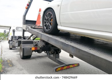 Broken down auto vehicle car towed onto flatbed tow truck with hook and chain