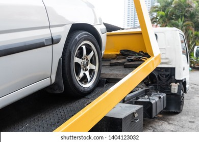 Broken down car being towed onto flatbed tow truck with cable for repair at workshop garage