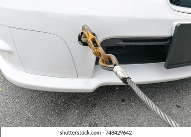 Broken down car fitted with hook and chain being towed by tow truck