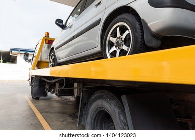 Broken down car on flatbed tow truck being transported to garage workshop for repair