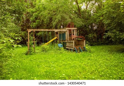 broken down playground equipment in overgrown yard