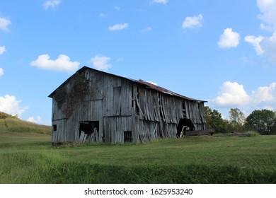 Broken down wood barn in field against blue sky.