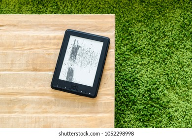 Broken ebook reader laying on the edge of wooden table