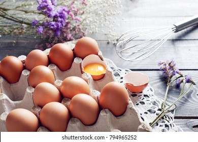 Broken egg among eggs in egg box