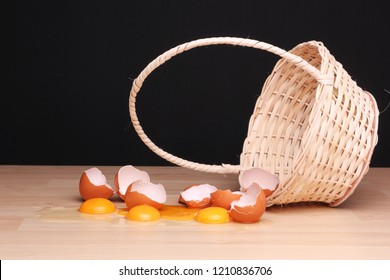 Broken eggs next to an overturned wicker basket.  The risk of having alll eggs in one single basket. (Shallow depth of field)