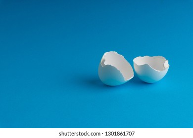 Broken eggshell on the blue background with selective focus