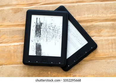 Broken electronic book readers on wooden table