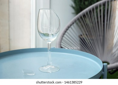 Broken empty goblet. A glass goblet on a leg stands on a small table on the terrace. A piece of glass lies near the cracked wine glass.