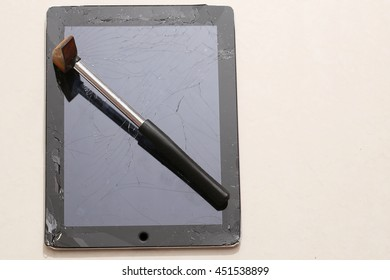 Broken flat glass of tablet and rusty hammer