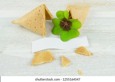Broken fortune cookie with blank label and four-leaf-clover, wooden background
