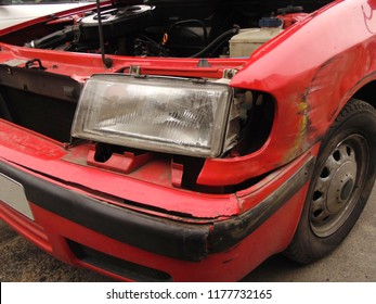 broken front side wing of a red car after an accident