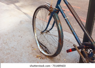 Broken front wheel with loose tyre on an abandoned rusty bicycle, locked to a metal pole.