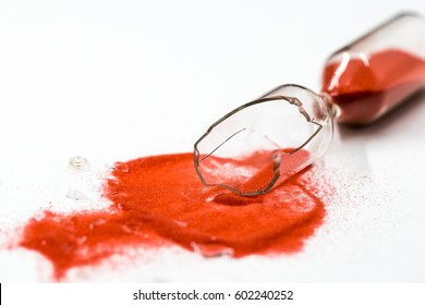 broken glass hourglass with red sand on a white background , time concept