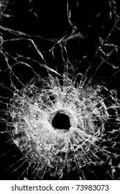 broken glass isolated on black - authentic bullet hole - close up