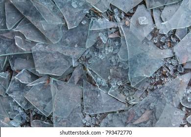 Broken glass litters pavement of vandalized building