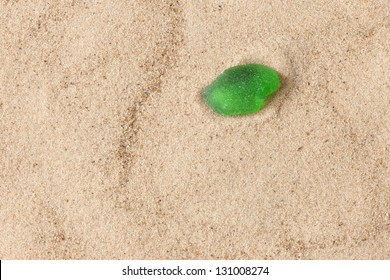 Broken glass lying on the sea sand