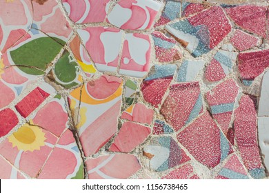 Broken glass mosaic tile colored pink background, decoration in Park Guell, Barcelona, Spain. Ceramic art