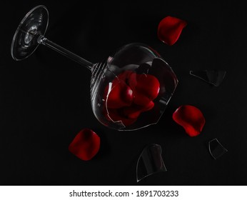 A broken glass and rose petals with shards lie diagonally on a black background, close-up top view.