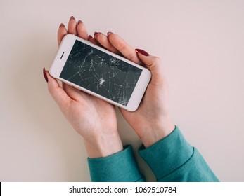 Broken glass screen smartphone in hand, white background.