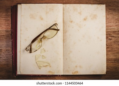 broken glasses on open old book blank, top view