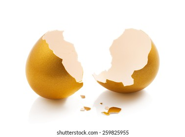 broken golden egg isolated on white background