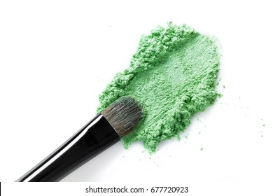 Broken green eye shadow and makeup brush isolated on the white background
