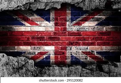 Broken grunge wall with British flag on old brick wall behind.