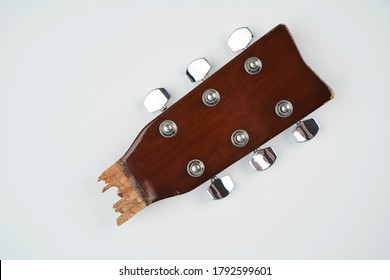Broken guitar neck on a white background with copy space. Broken acoustic guitar headstock, close-up. Guitar repair and service
